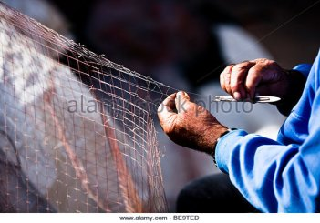 close-up-of-senior-man-carefully-mending-fishing-net-be9ted